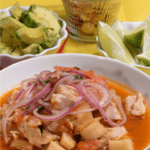 A beautiful bowl of Ecuador Fish soup served with avocado and toasted corn kernels