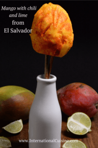 A mango on a stick, cut to look like a flower in a vase with chili and lime.