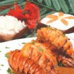 A stunning presentation of two lobster tails in a coconut curry sauce.