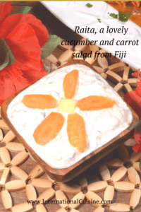 A bowl of creamy raita decorated with a flower made from carrot slices