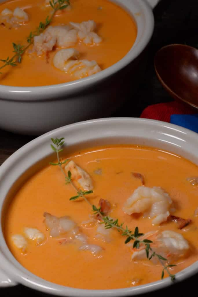 A picture of Icelandic lobster soup a rich orange color with chunks of shrimp and lobster, garished with a sprig of thyme.