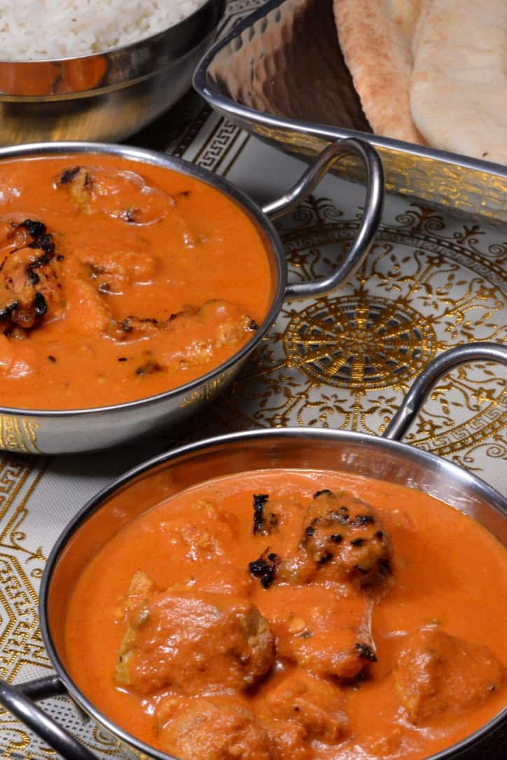 A picture of Indian chicken butter masala bright oranage sauce with chunks of chicken ready to sop up with naan bread