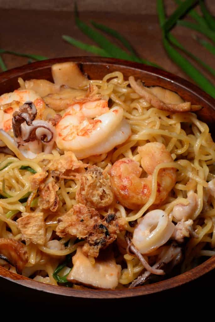 A picture of a bowl of Indonesian Bakmi Goreng, noodles with shrimp, squid, mushrooms and fried onions.