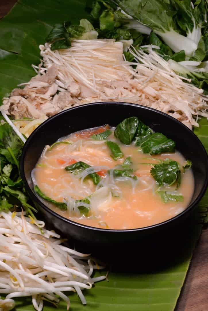 A picture of a bowl of Laotian coconut noodle soup surrounded by mushrooms, greens and bean sprouts served on a banana leaf.