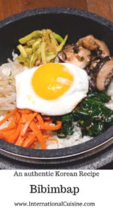 a bowl of bibimbap with rice, a cooked egg and surrounded by seasoned vegetables