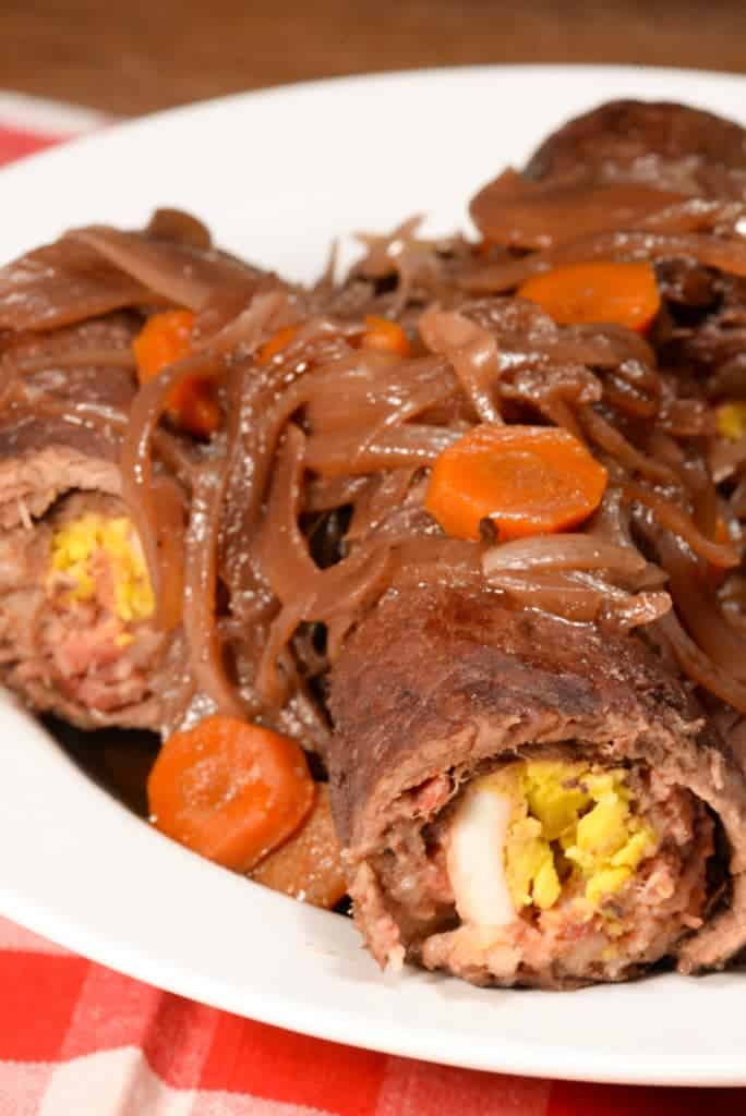 olives mushrooms and onions rolled up in beef topped with onions and carrots.