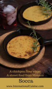 Monaco socca a crepe in a cast iron skillet with a twig of rosemary