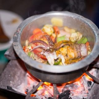 A pot of calamari curry cooking over charcoal
