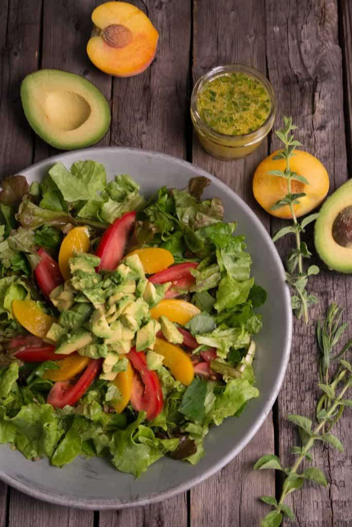 A picture of  Mozambican Avocado Salad fresh lettuce, tomatoes, peaches of course avocado slices alongside a lemon dressing.