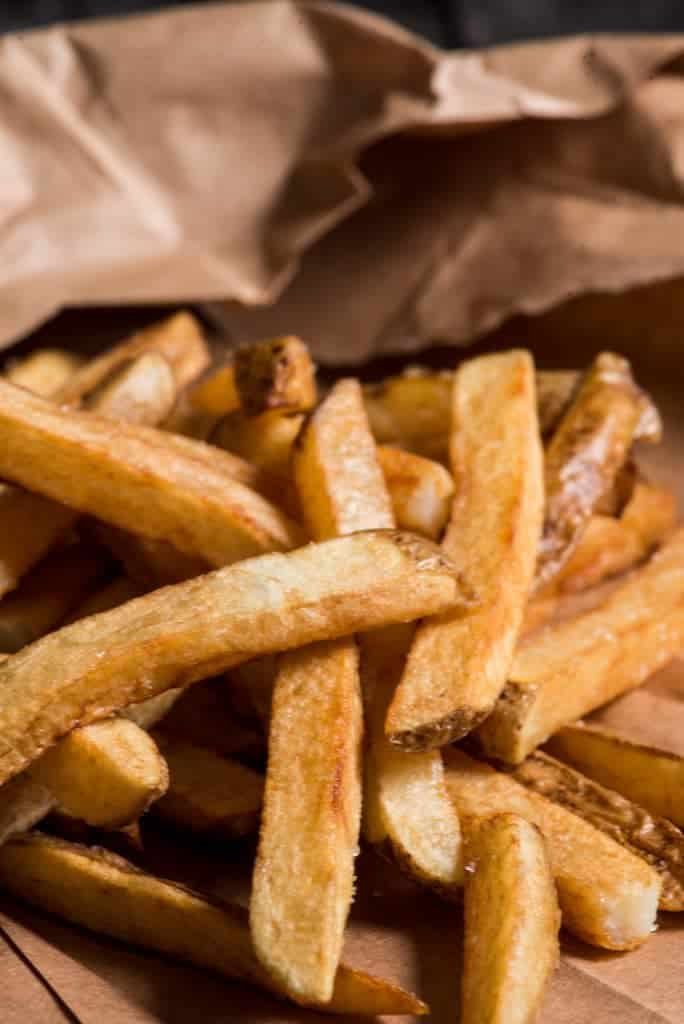 A picture of just fried Mozambican chips or fries, thick potato fries with a hint of skin on