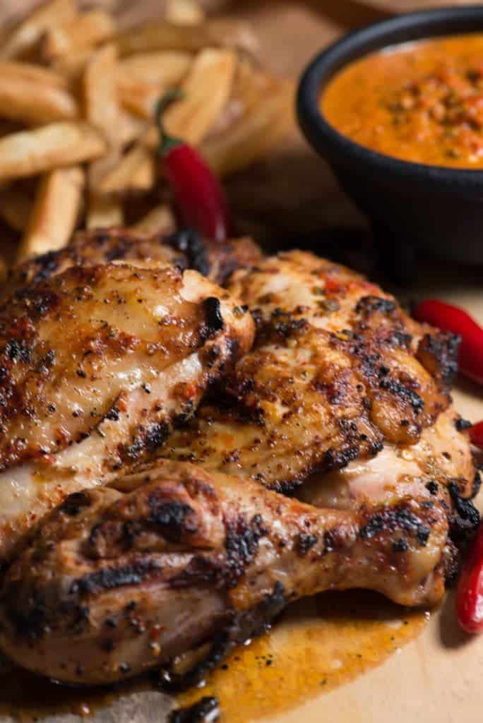 A picture of grilled chicken smothered in peri-peri sauce on a plate with fries and more peri peri sauce for dipping