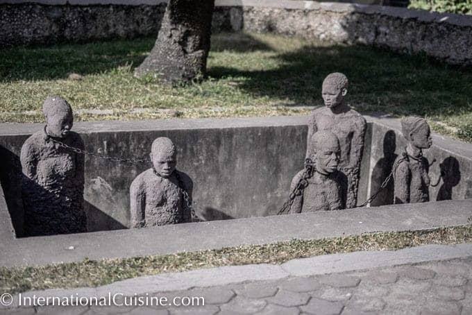 Statues of black men in a pit with chains around their necks at the Slave Trade Memorial in Zanzibar