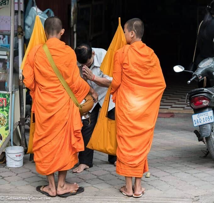 Monks in bright orange robes receiving alms
