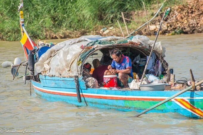 A coloful boat filled with a fisherman and his family