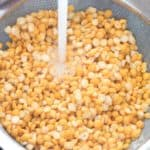 A strainer full of yellow split peas being rinsed