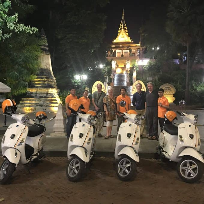 vespa scooters lined up in front of temple all lit up
