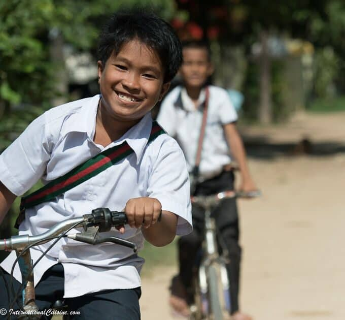 School boys with big smiles in uniforms riding bikes