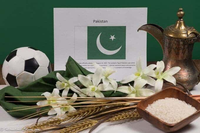 A picture of the flag of Pakistan with a soccer ball, rice and wheat along with jasmine.