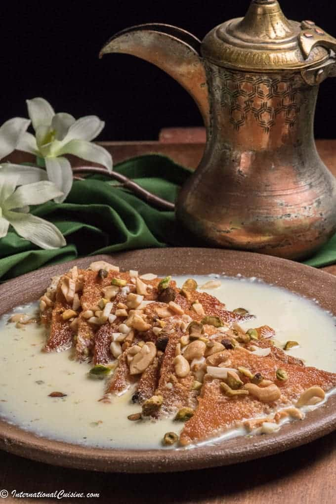 a plate of shahi tukra, fried bread covered with milk and nuts