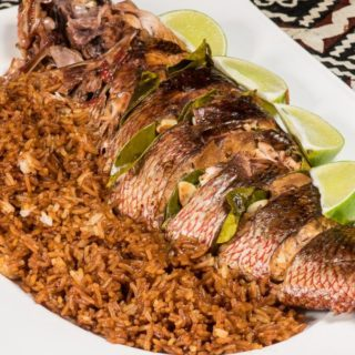 A snapper fish plated with rice and lime