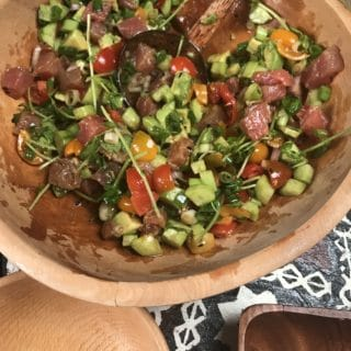 a bowlful of fresh chopped, tomatoes, shallots, cucumber, avocado and fresh ahi tuna, a colorful poke salad