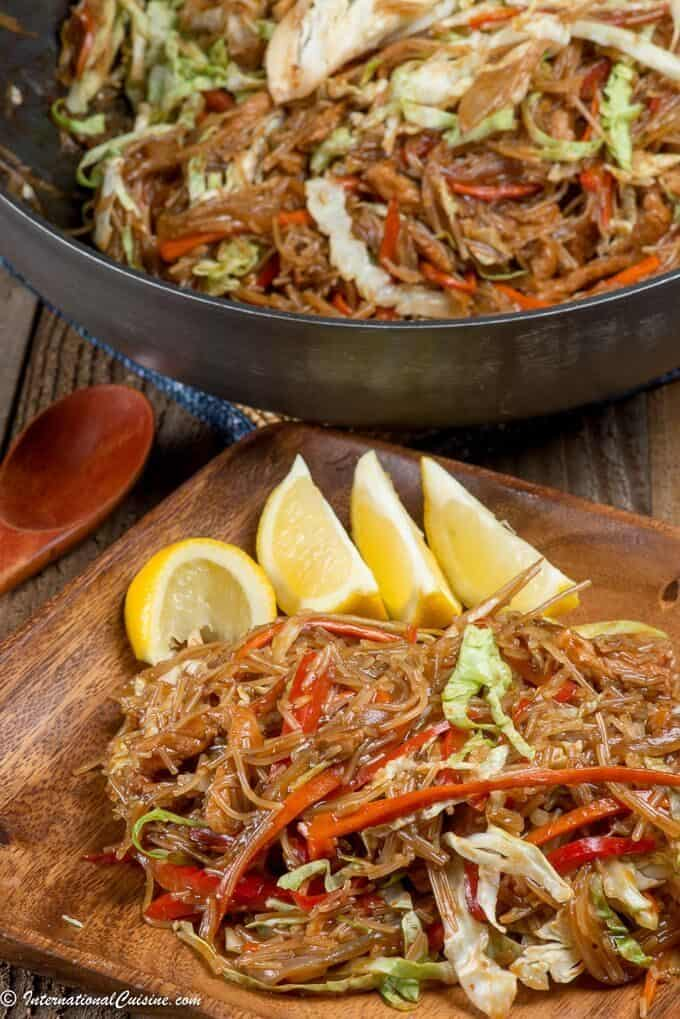 A plate of pancit noodles with pork and vegetables