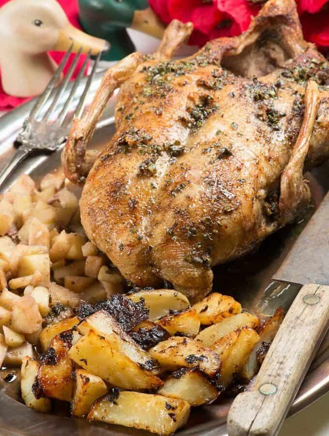 a whole roasted duck on a platter with apples and crispy potatoes