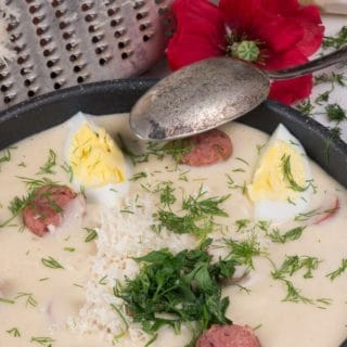 a bowl of polish white borscht soup garnished with eggs, dill, and grated fresh horseradish