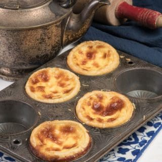4 beautiful pais de nata custard tarts in a muffin pan.
