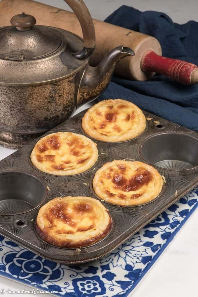 4 beautiful pais de nata custard tarts in a muffin pan.