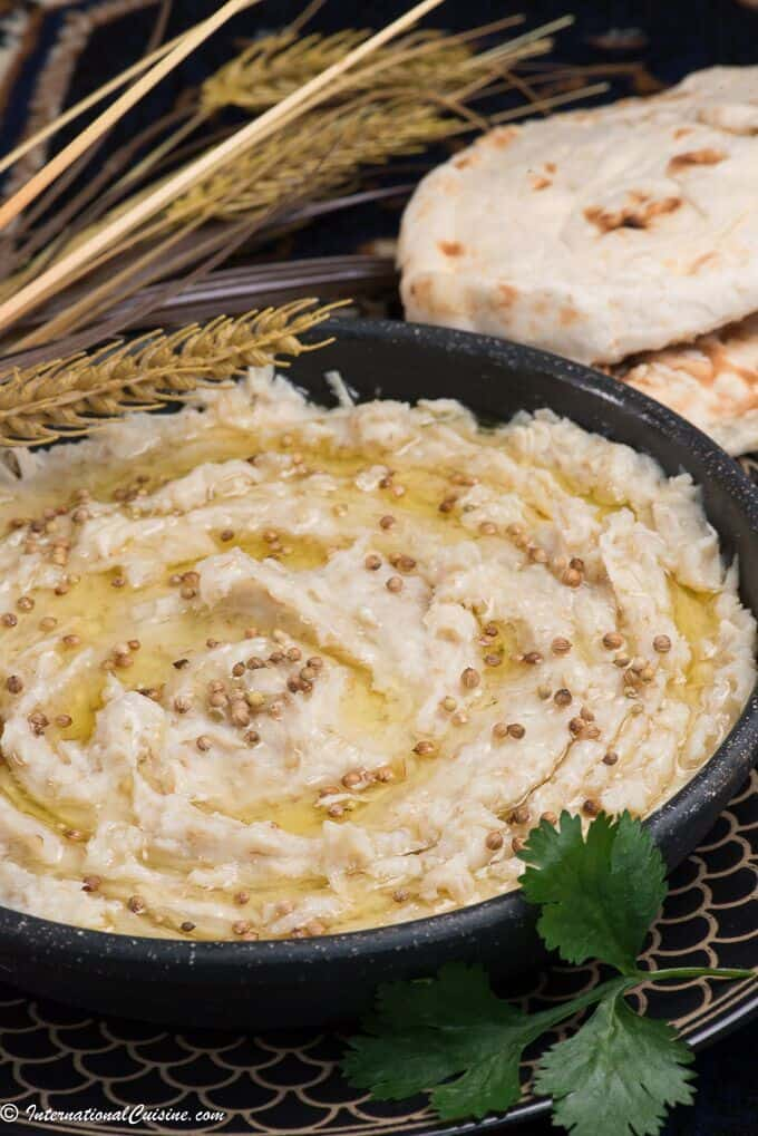 a creamy bowl of qatari harees that is drizzled with ghee and coriander seeds.