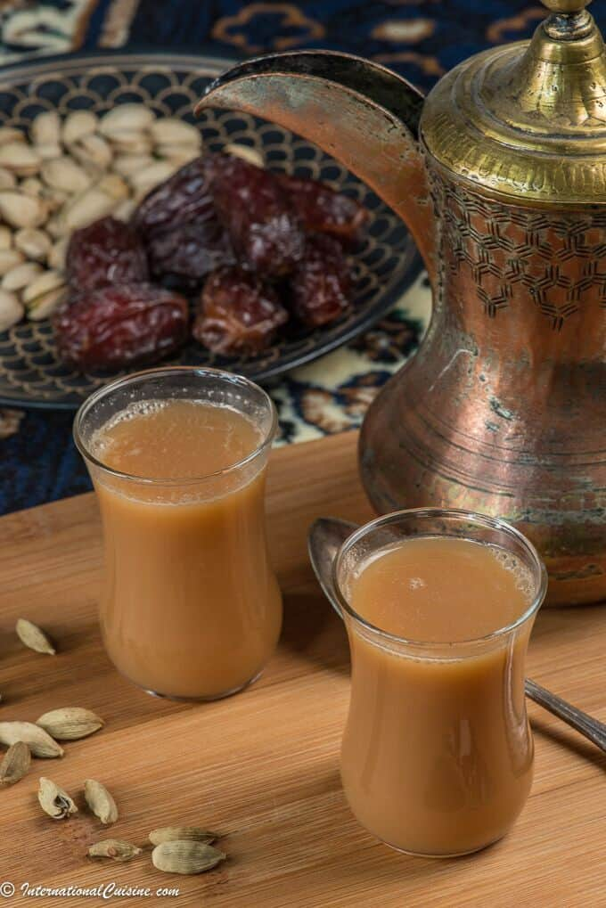 two cups of milky qatari karak tea surrounded by cardamom pods