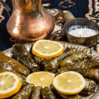 A plate full or warak enab stuffed grape leaves on a platter garnished with lemon wedges
