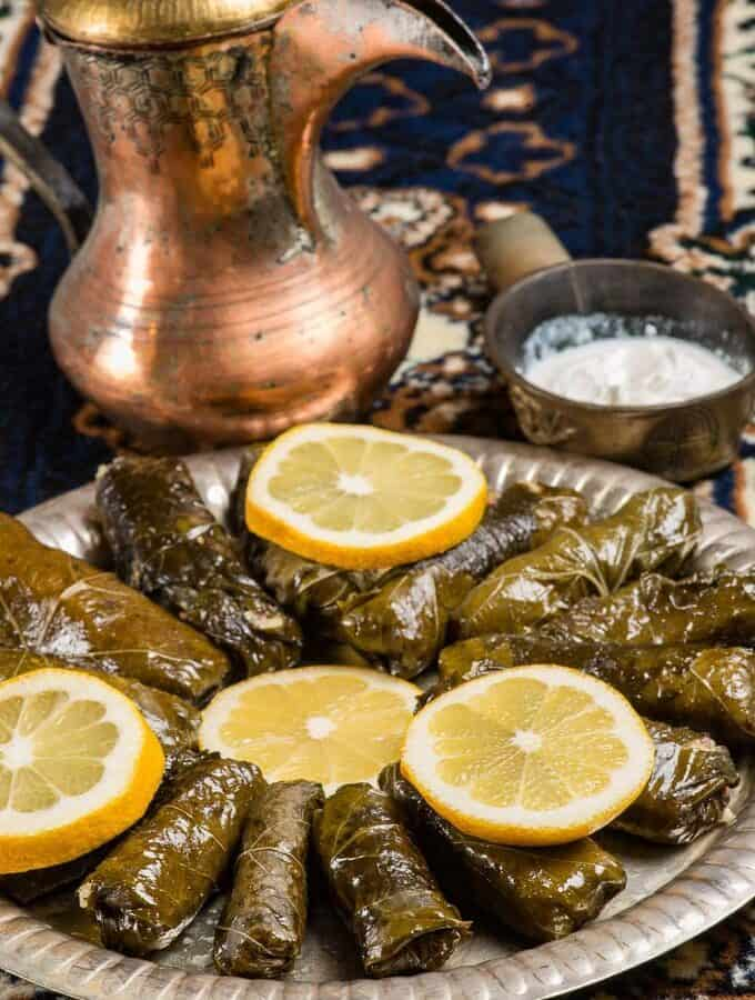 A plate full or warak enab stuffed grape leaves on a platter garnished with lemon wedges