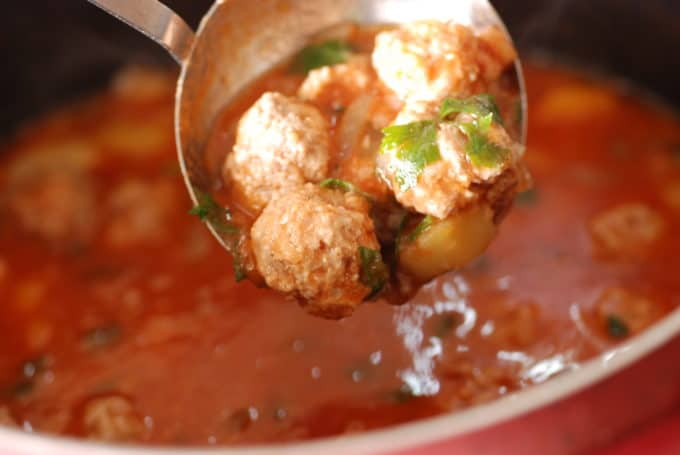a ladle full of Romanian meatball soup