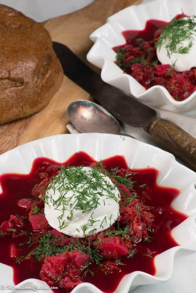 A bowl of Russian borsht with a scoop of sour cream and garnished with dill