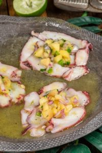 a plate of octopus carpaccio topped with mango salsa