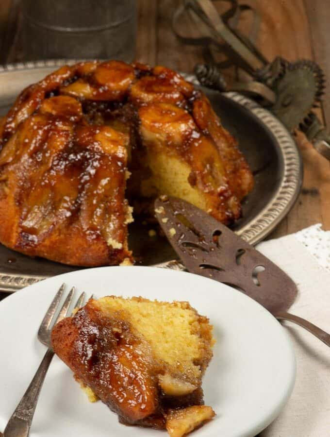 A cake smothered with caramel and bananas