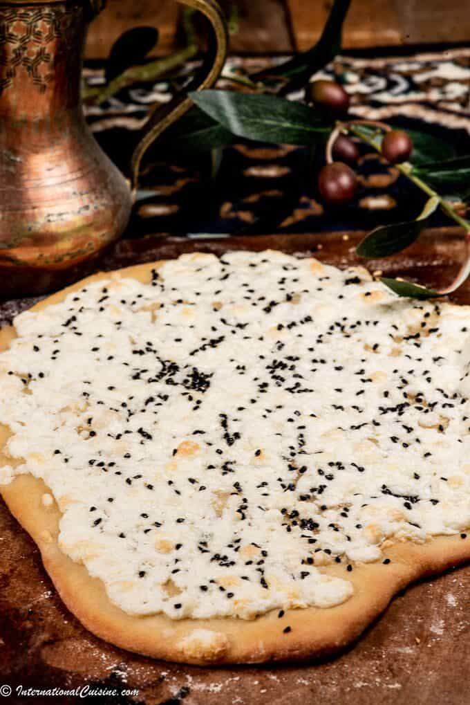 A flat bread with baked cheese and nigella seeds
