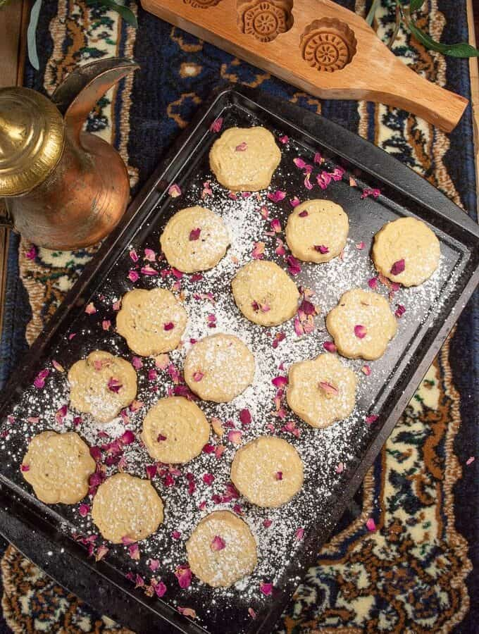 A cookies sheet ful of beautiful ma'amul cookies covered with powdered sugar and rose petals.