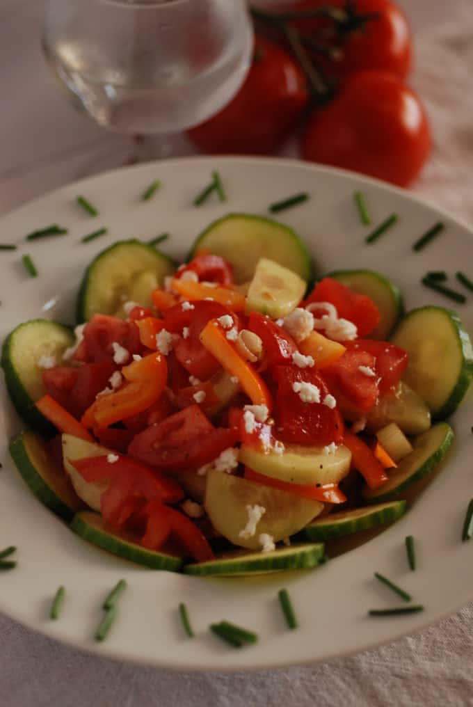 a bowl of Serbian salad with cucumbers, tomatoes, peppers and cheese