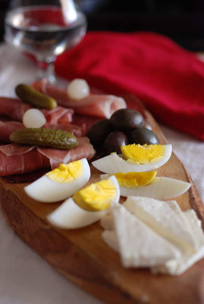 A picture of Serbian Meze cured meats, cheese, olives, pickled onions and eggs