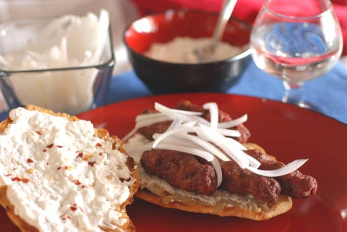 A picture of Serbian flat bread, topped with kaymak, cevapi, and onions.