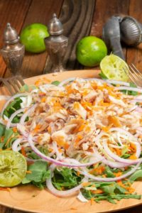 a big plate of smoked fish salad with onions, carrots, cabbage on a bed of arugula