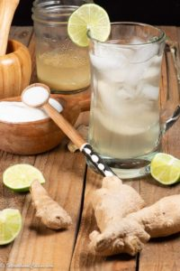 A glass of Sierra Leone Ginger beer surrounded by the ingredients.