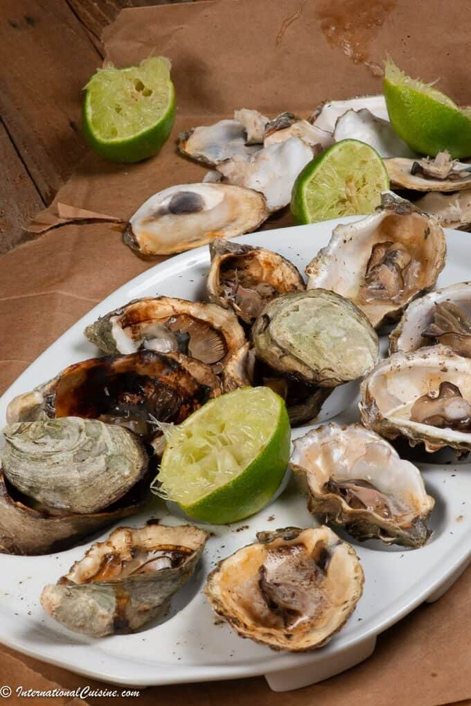 a plateful of freshly grilled oysters with squeezed lime