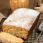 A ginger cake topped with confectioners sugar cooling on a baking rack