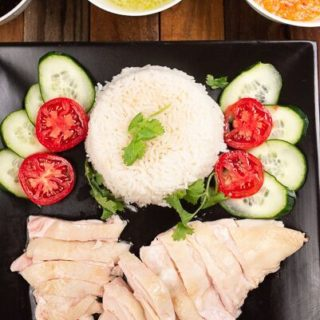 A plate of Hainanese chicken rice with three sauces, surrounded by cucumber and tomato slices.