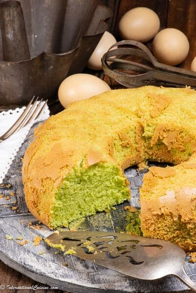 A pandan chiffon cake with a piece missing.