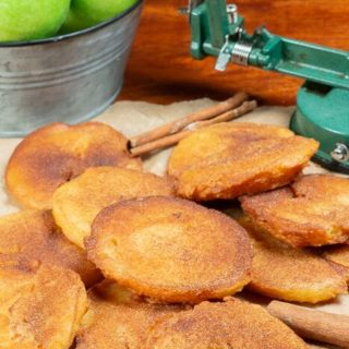 a bunch of fried apple slices topped with cinnamon and sugar.